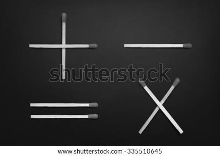 Basic mathematical symbols - plus, minus, multiplication & equal - on black chalkboard - stock photo