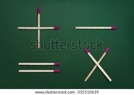 Basic mathematical symbols - plus, minus, multiplication & equal - on green chalkboard - stock photo