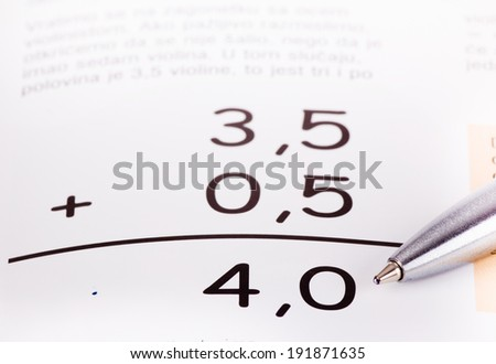 Basic summing of decimal numbers with pencil pointing at result - stock photo
