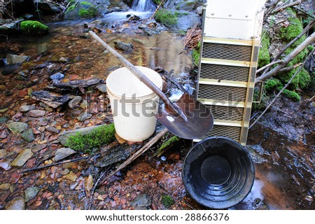 Basic tools used for placer gold prospecting. These include a gold pan, sluice box, 5 gallon plastic bucket and a shovel. A peaceful mountain stream is used for a backdrop. - stock photo