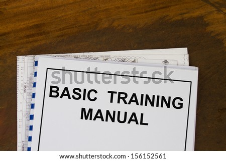 basic training manual with blueprints in a wood texture background. - stock photo