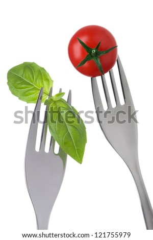 basil and cherry tomato on forks against white background - stock photo