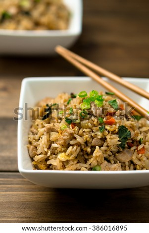 Basil chicken fried rice with chopsticks on a wooden background viewed from above. This thai inspired meal is perfect for a quick lunch or served as side dish. - stock photo