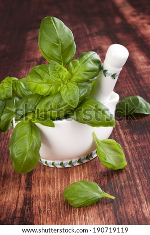 Basil. Culinary herbs. Fresh basil bunch in mortar with pestle on brown wooden background. Traditional cooking, rustic style. - stock photo