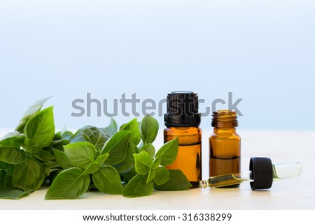 Basil essential oils in bottles - stock photo