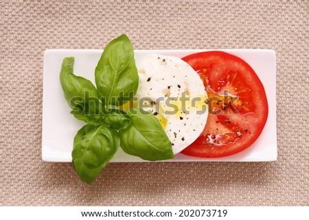 Basil leaf, mozzarella cheese, tomato slice, top view - stock photo