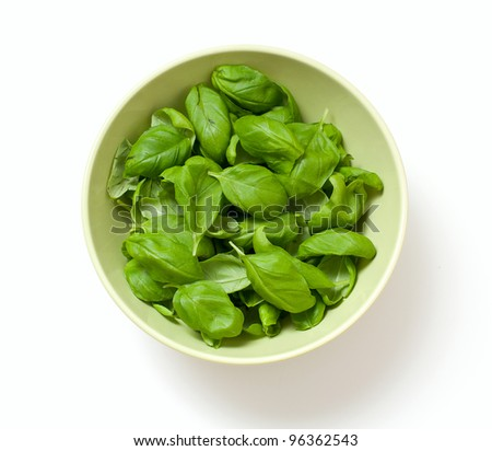 basil leafs in a green bowl isolated on white - stock photo