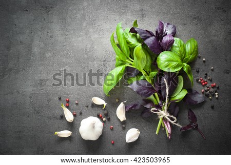 Basil leaves, garlic, pepper at dark slate background. Space for text. Ingredients for cooking. - stock photo