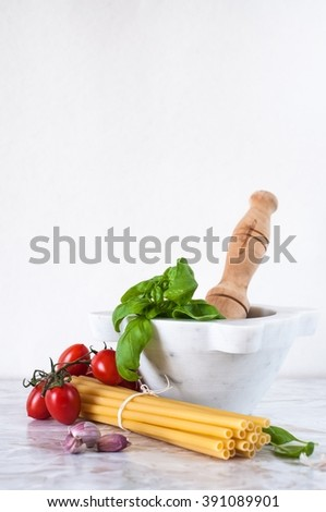 basil leaves in a white mortar, garlic, tomatoes and pasta: Italian food