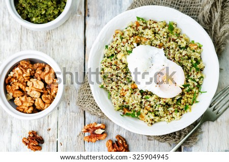 Basil nuts pesto quinoa with walnuts, parsley and poached egg. toning. selective focus - stock photo