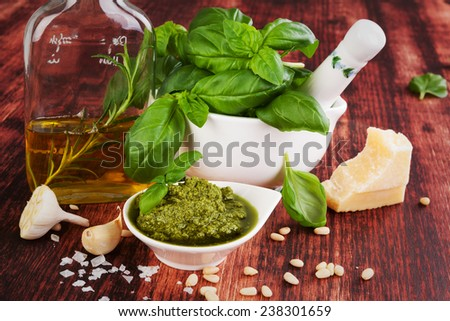 Basil pesto, fresh basil leaves, garlic, pamrmigiano cheese, olive oil and pine seeds on wooden background. Green pesto still life, country style. - stock photo
