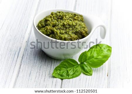 basil pesto in ceramic bowl on kitchen table - stock photo