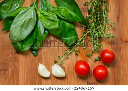 Basil, thyme, cherry tomatoes and garlic on a board