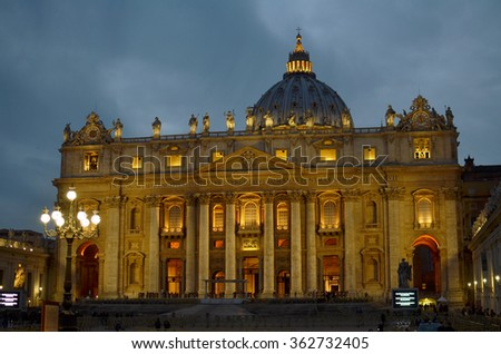 "Basilica of St. Peter's in Vatican at night, in Rome, Italy. Foreign text means: ""In honor of the prince of Apostles; Paul V Borghese, Pope, in the year 1612 and the seventh year of his pontificate"" - stock photo"