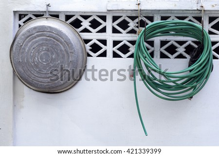 Basin and green hose are the white wall.  - stock photo