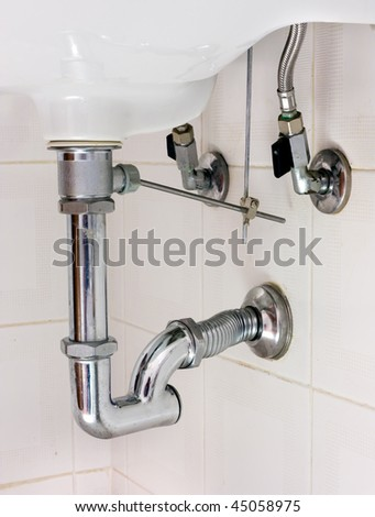 basin drainer, siphon with p-trap and insert for pop up waste, washbasin in bathroom - stock photo