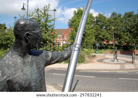 BASINGSTOKE, UK - AUGUST 26, 2007: L'Arc statue by David A Annand in Basingstoke, Hampshire.  Two bronze figures hold arcs of steel creating a gateway across the road.  On public display since 1999. - stock photo