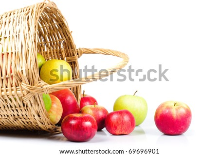 Basket and apples are scattering on white background. Symbol of autumn - stock photo