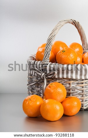 Basket and stack of fresh tangerines on silver background