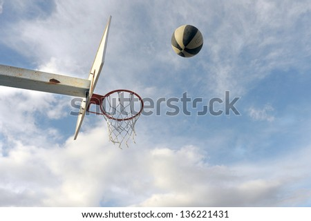 basket ball board under blue sky with white clouds and ball - stock photo