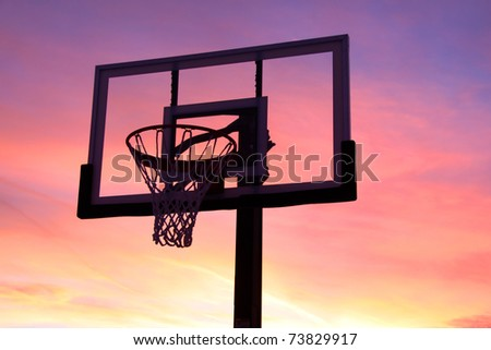 Basket ball hoop against bright orange sky background - stock photo