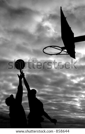 Basket ball players silhouetted against the sky - stock photo