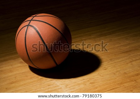 Basket ball sitting on basket court in the spotlight. - stock photo