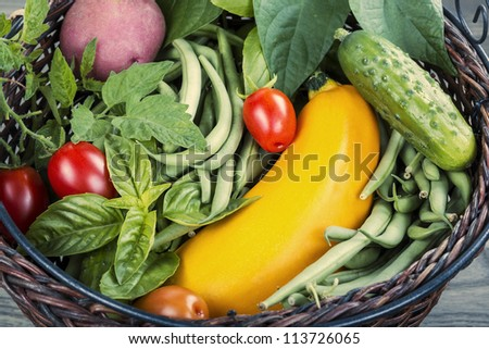 Basket consisting of green beans, tomatoes, potato, basil and zucchini - stock photo