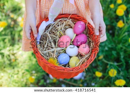 Basket Easter eggs in girls hand on spring day - stock photo