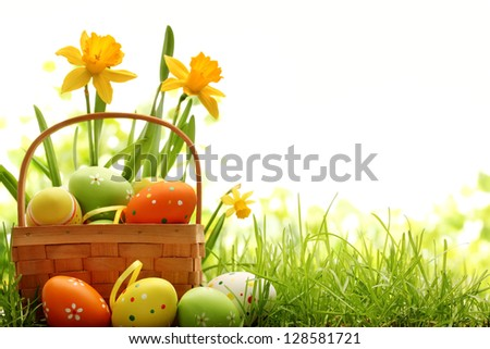 Basket filled with easter eggs on meadow with daffodil - stock photo