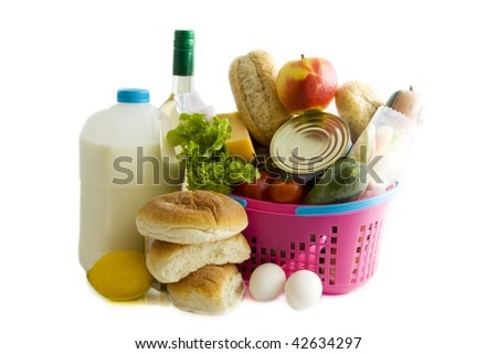 Basket filled with groceries isolated over white - stock photo
