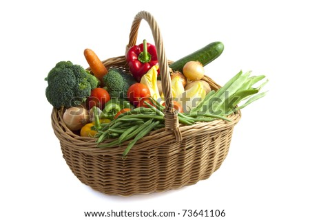 Basket filled with lots of vegetables isolated over white - stock photo