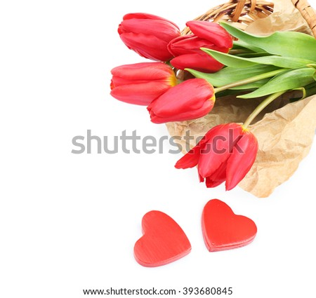 Basket filled with red tulips isolated on white - stock photo
