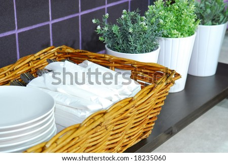 Basket filled with tableware to set tables at a restaurant - stock photo