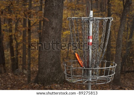 Basket for Disc Golf in a Forest during Fall Colors. An orange disc is in the basket. - stock photo