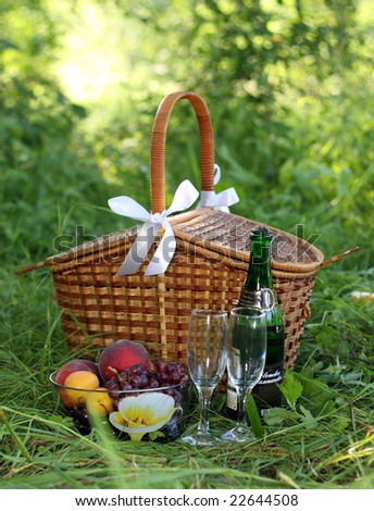 basket for picnic with champagne and fruits