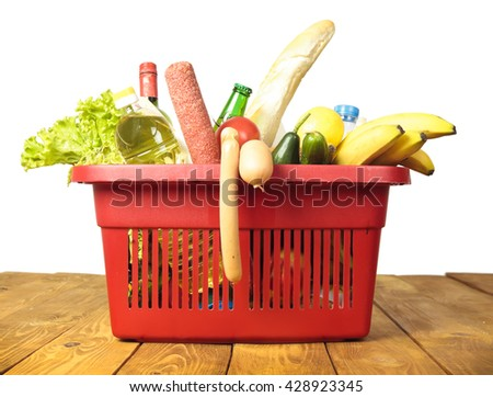 Basket from supermarket and many products therein - stock photo