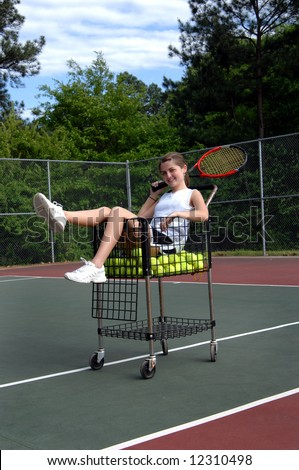 Basket full of balls and tennis player.  Female teen poses with racket in basket. - stock photo