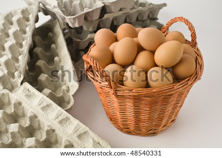 Basket full of brown eggs surronded by empty egg cartons - stock photo
