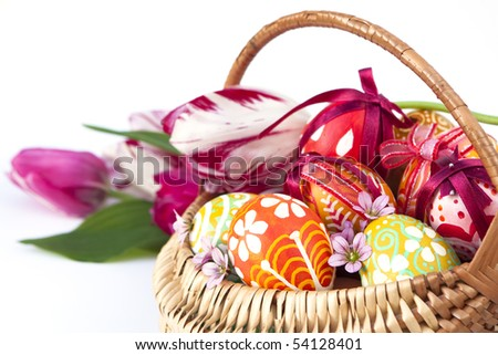 Basket full of Easter eggs and tulips - stock photo