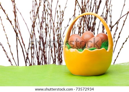 Basket full of Easter eggs and willow twig - stock photo