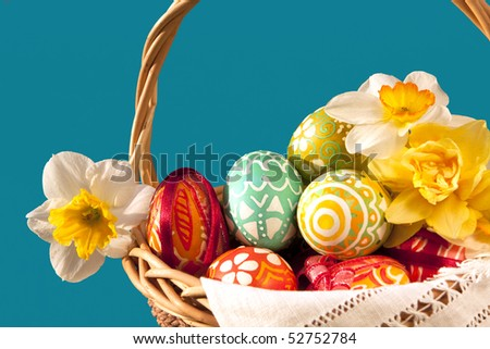 Basket full of Easter eggs and yellow spring daffodils - stock photo