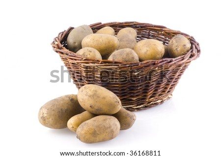 Basket full of potatoes, with a few next to it, isolated on white.