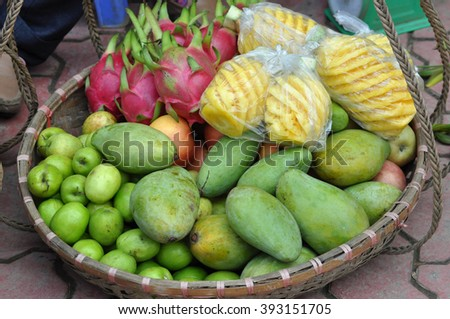 Basket full with exotic fruits in a market. Vietnam - stock photo