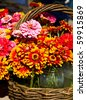 Basket holding jars of Zinnias for sale at a local farmer's market - stock photo