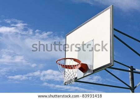 Basket hoop in a blue sky - stock photo