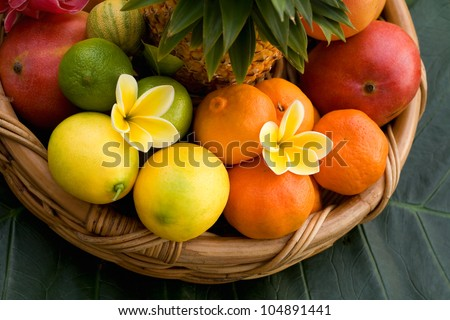 Basket of assorted tropical fruits and tropical flowers - stock photo