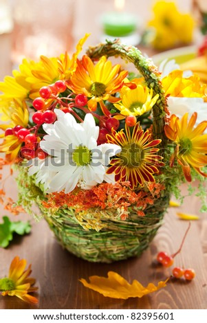 basket of autumn flowers on the wooden table - stock photo