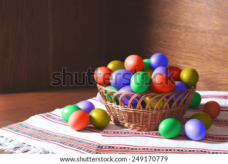Basket of beautiful easter eggs in a woven basket. Easter stock image - stock photo