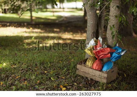 Basket of brazilian Easters eggs under a tree. - stock photo